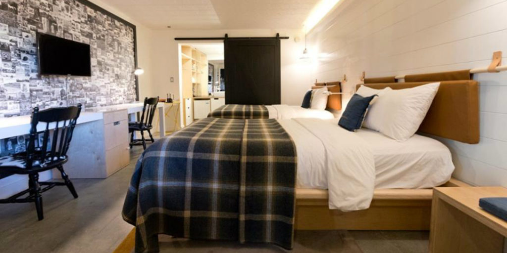 farm style hotel room with double beds draped in blue and cream farm inspired bedding
