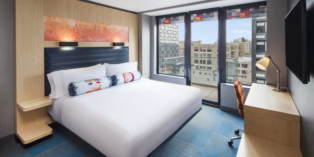hotel room with light colored furniture and a walk on balcony overlooking a city