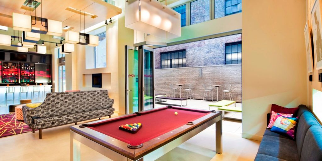 open airy loung area with red pool table, dark softa seating, and red lit bar in the background