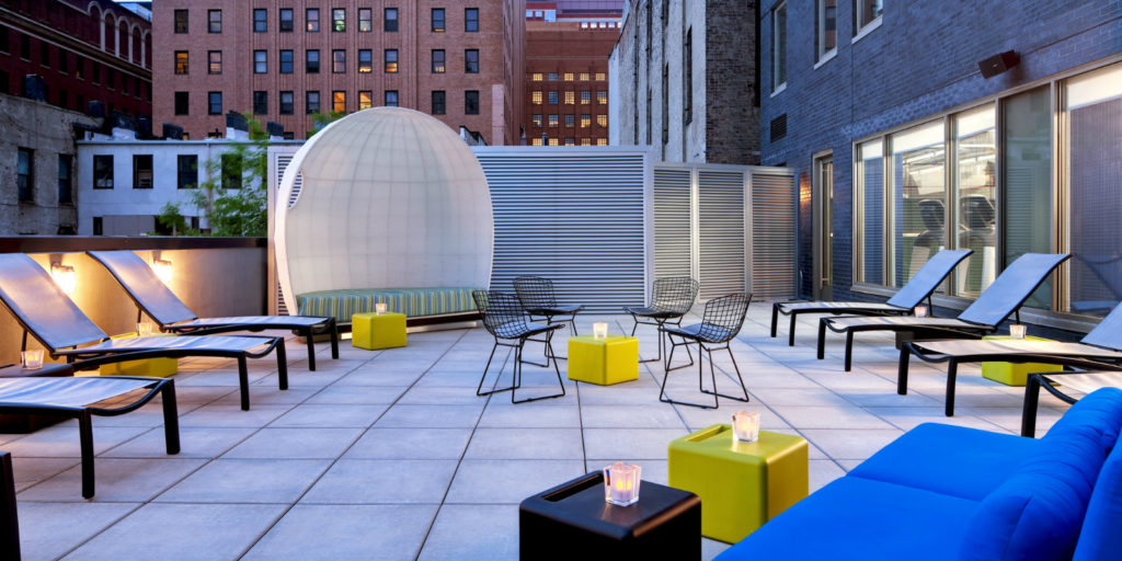 rooftop patio with white and black lounge chairs, black metal frame chairs, and yellow square side tables