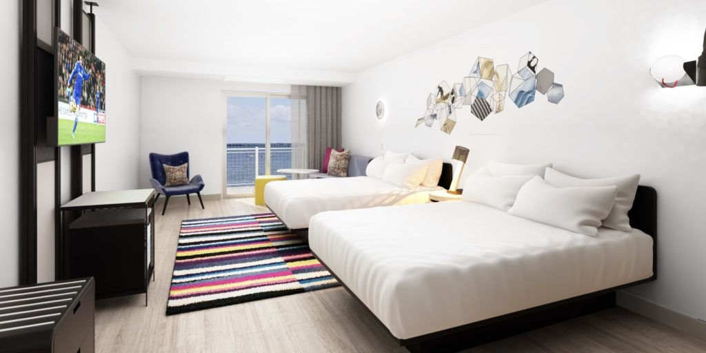modern bedroom with two queen beds, light colored tile floors, white walls and balcony view of water
