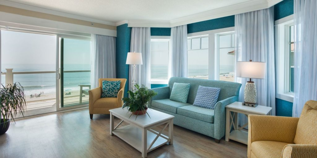 an oceanfront room decorated with a blue sofa, tan armchair and light wooden coffee table