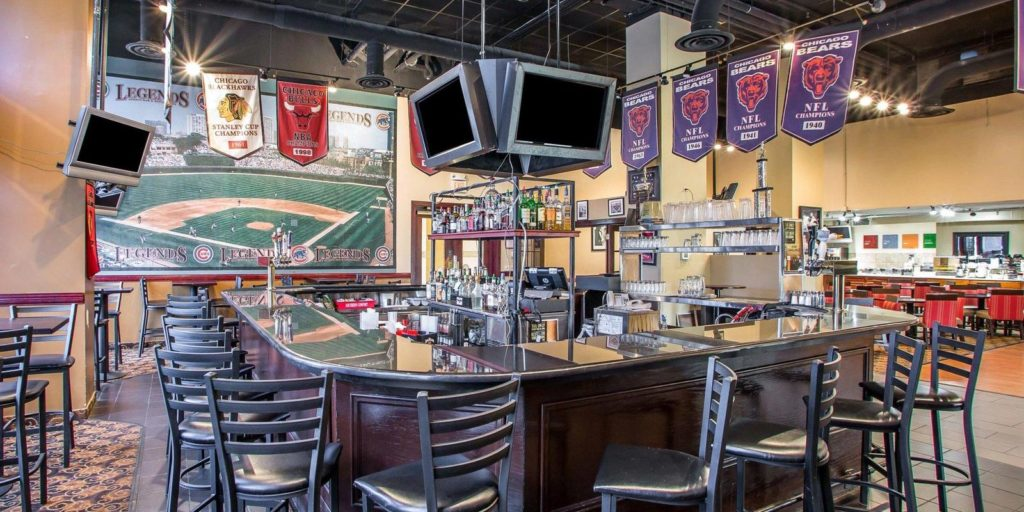 suare shaped sports bar surrounded by black barstools, sports banners and televisions