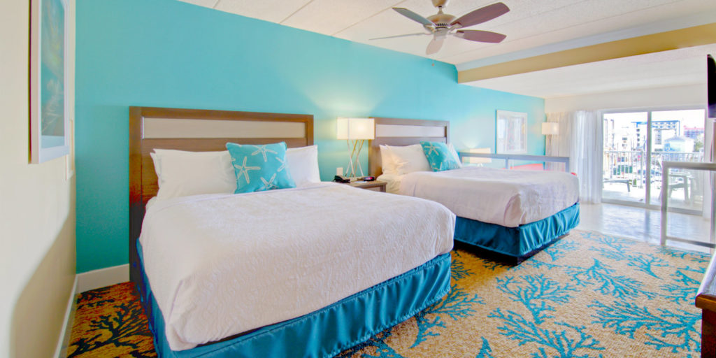 a beach themed hotel room with tan carpet and blue coral and a turquoise accent wall set behind two queen beds