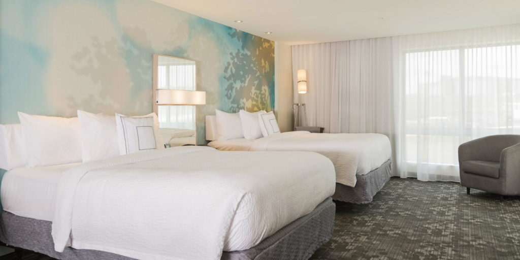 two queen beds with white bedding and light gray bed skirts in a room wiht gray patterned carpeting and chair