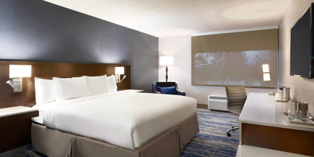a sleek modern hotel room with gray blue accent wall behind a large king bed and long wooden headboard