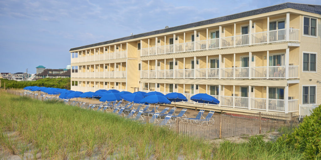 standing on a beach dune looking at a three story yellow hotel building with blue beach umbrellas and blue lounge chairs on the sandy lawn
