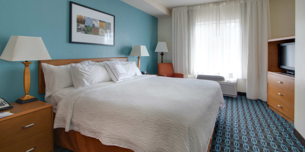 light honey colored bedroom furniture and a quite king size bed set on blue and brown patterened carpeting