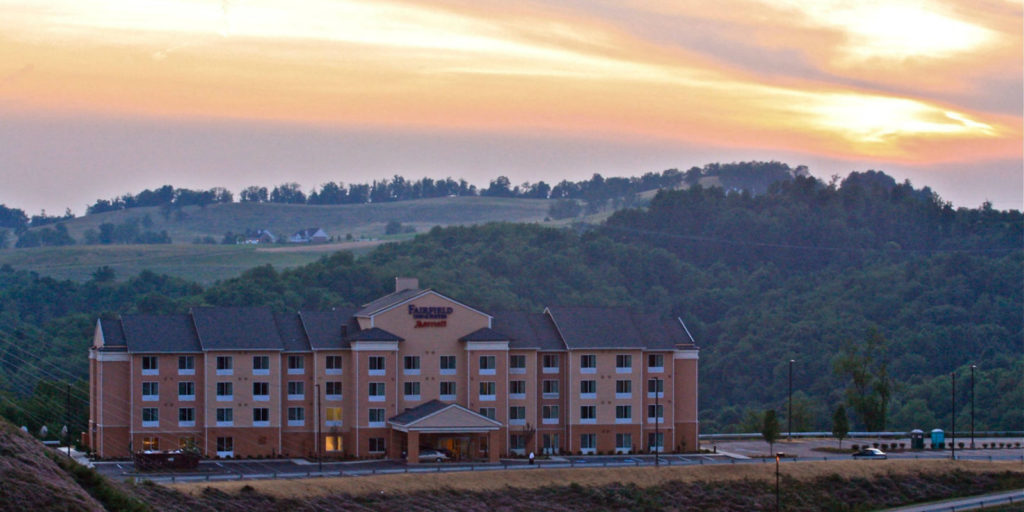 view of a four story hotel set infront of a mountain view at sunset
