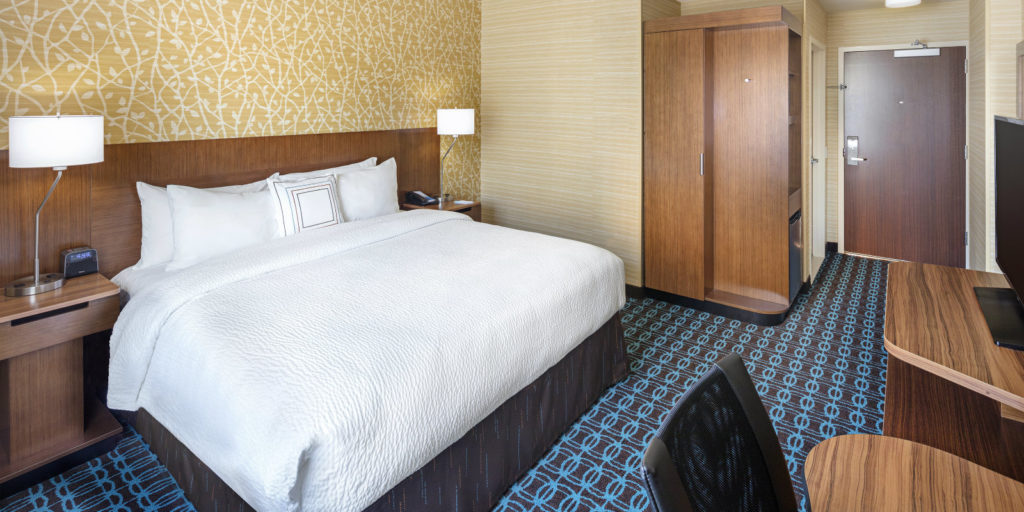large king bed set in a hotel room with blue and brown patterned carpet and a gold and white textured wallpaper
