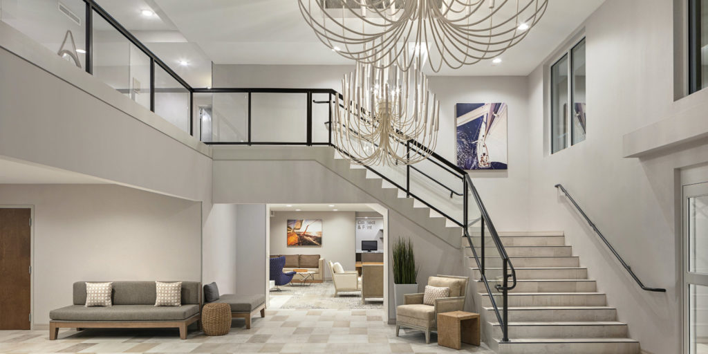 light colored lobby area with grand staircase leading to the second floor and balcony and large all white chandaliers