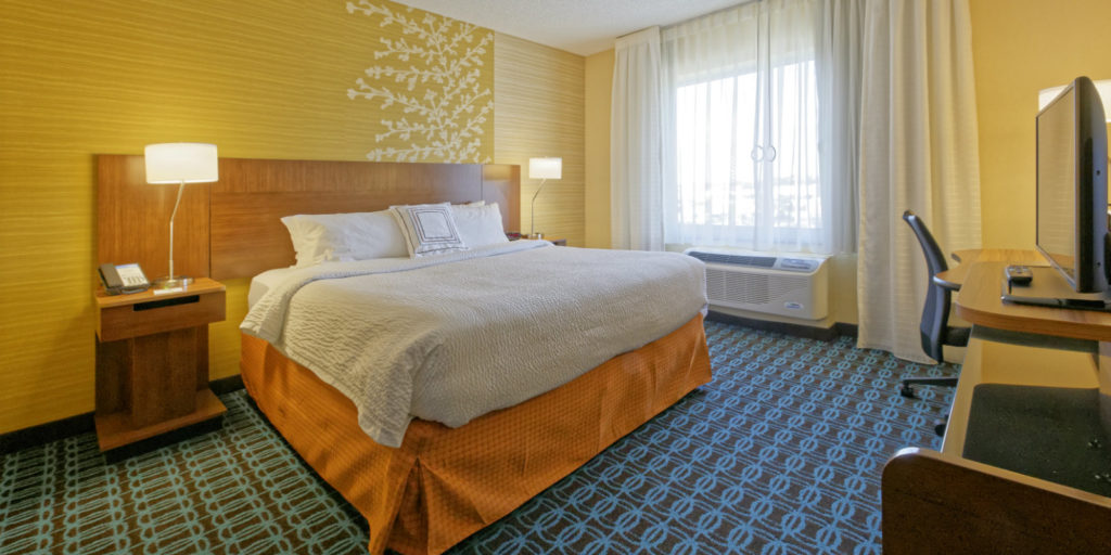 a hotel room decorated in golden yellows, oranges and blue with floral accents on the wall behind the bed