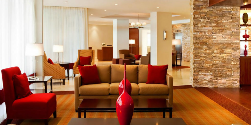 lobby area of a hotel that includes sofas and armchairs for seating plus coffee tables and tall red vases