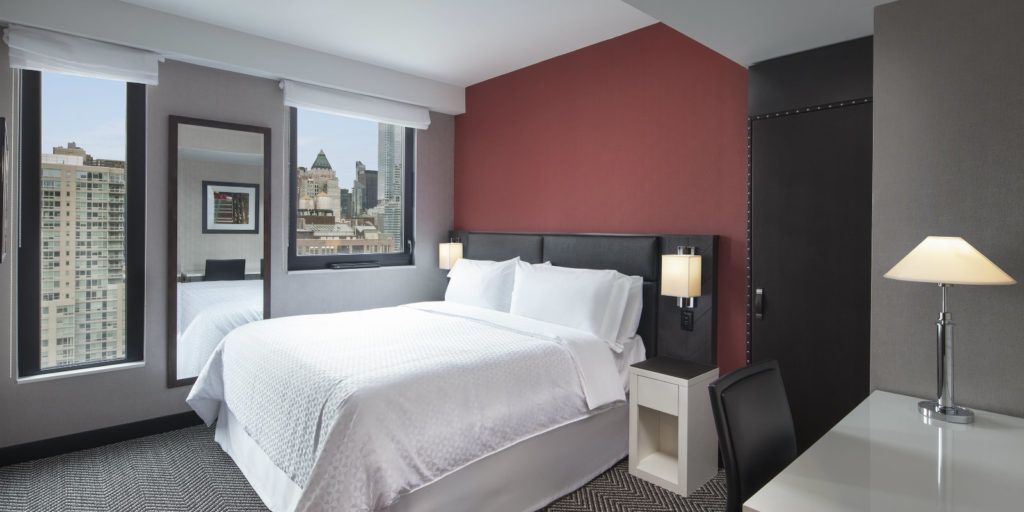 well lit bedroom with dark red accent wall and gray walls plus two windows to overlook the city view outside