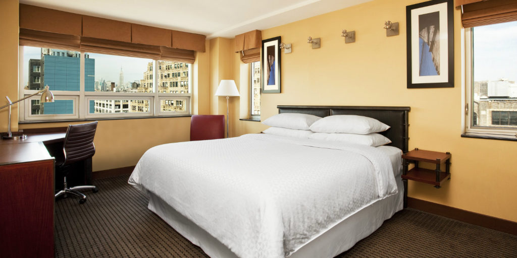 bedroom with large queen bed and honey colored walls with several windows overlooking a city view on a cloudy day