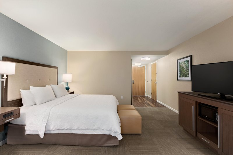 simplistic large hotel suite with king size bed with a modern headboard and dark wooden furniture