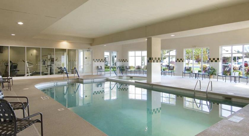 indoor swimming pool with black patio furniture and adjoining fitness center