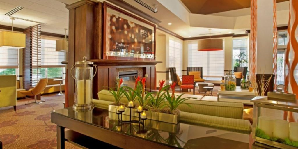 bright hotel lobby with light green and yellow accents, sofas, lounge chairs and booth seating