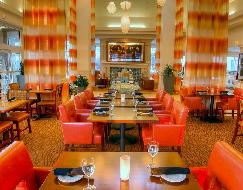 dining area decorated with bright oranges and golds with white chandaliers of different shapes hanging from the ceiling