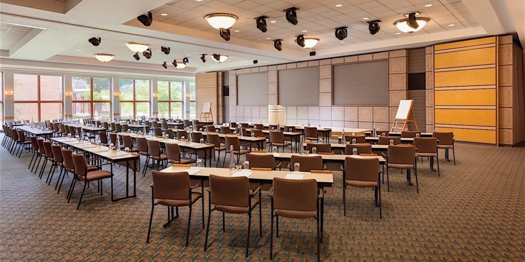 a large and open conference room with tables and chairs set up in classroom style seating facing a moderator post
