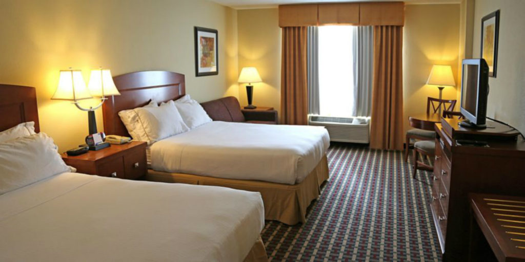 medium tone wooden furniture set in a hotel room with two queen beds and checked pattern carpet that includes offwhite, burgundy and slate blue colors