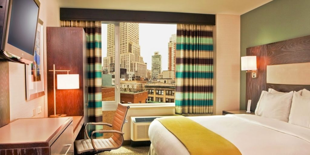 a very colorful hotel bedroom with a large window overlooking a city scape on a cloudy day