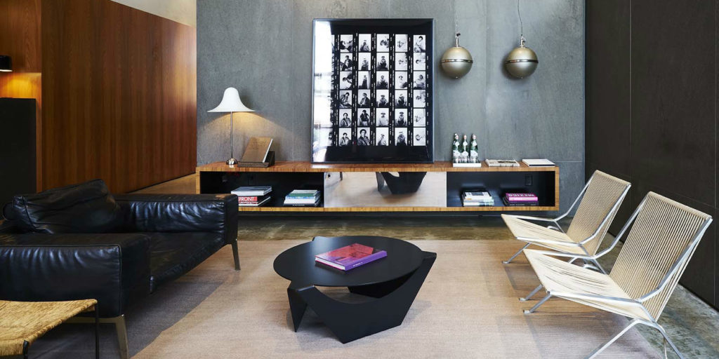 a 70's inspired seating area that includes a large black leather armchair and artistic round black coffee table and two metalic chairs