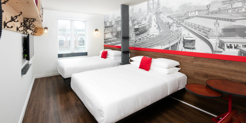 modern hotel room with a mural of a vintage scene of a railroad bridge running through a city