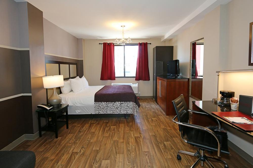 eclectic hotel room with red curtains on the window, queen bed with a plum colored quilt, small desk with office chair