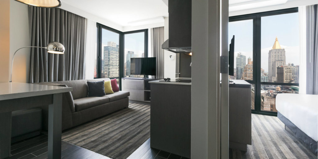 split view of a hotel room bedroom and suite area with various shades of gray furniture overlooking a large city