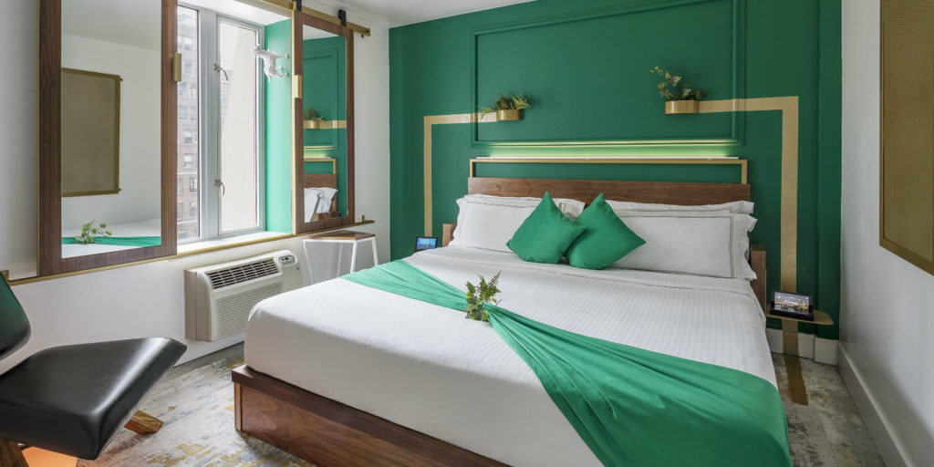 an art deco style hotel room with emerald green accent wall and gold accents
