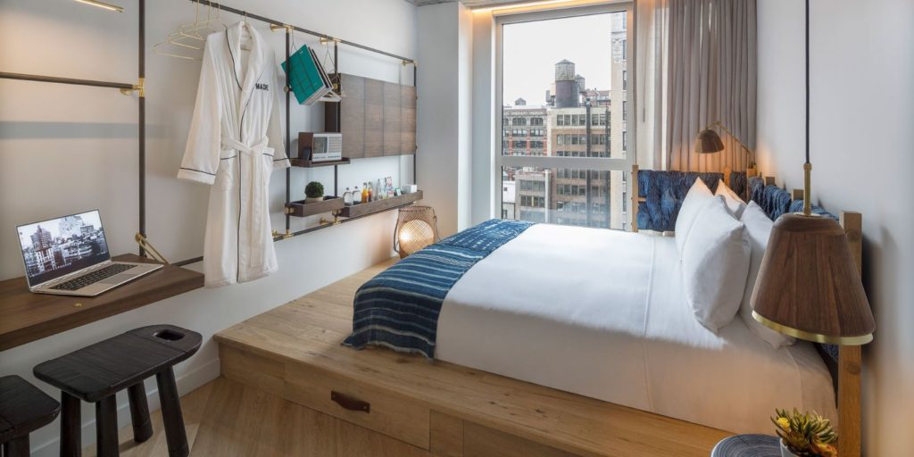 cozy hotel room overlooking a downtown industrial city scene with eclectic wooden furniture and accents
