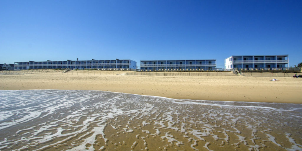 several two story blue hotels from the view of the ocean with sand, dunes and water