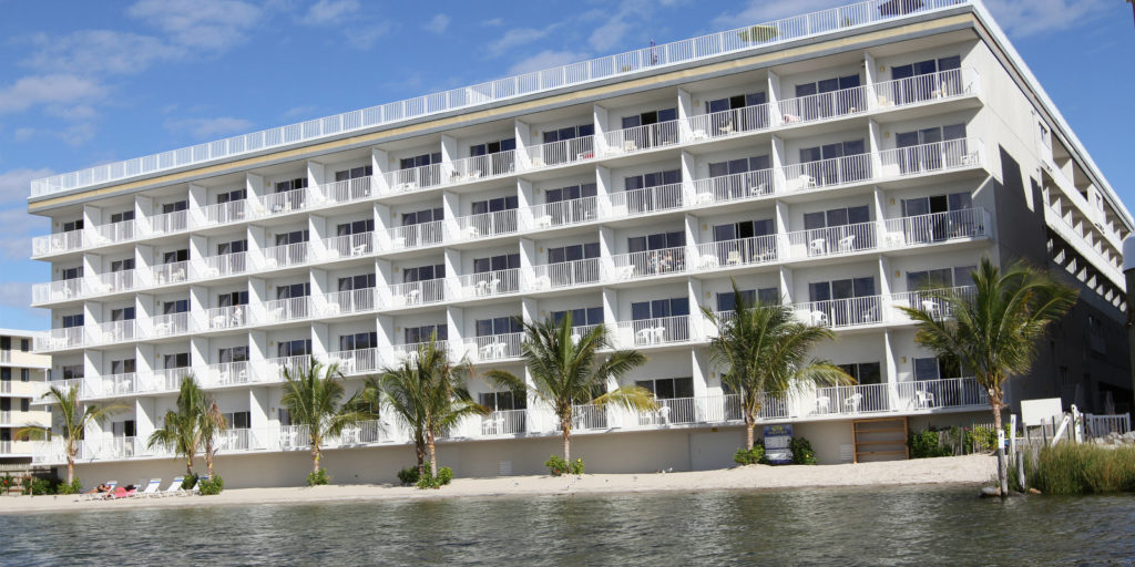 view of a five story white hotel and palm trees from a bay cove
