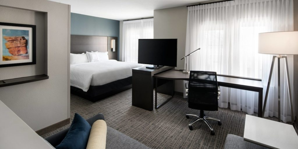 modern hotel room with gray and slate blue accents, office furniture, sectional sofa and large king bed