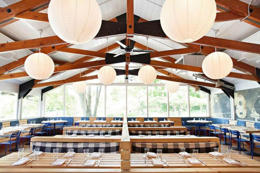 an dining area with wooden beams, round white paper lanterns and light wooden booths surrounded by large windows overlooking trees and a lawn area
