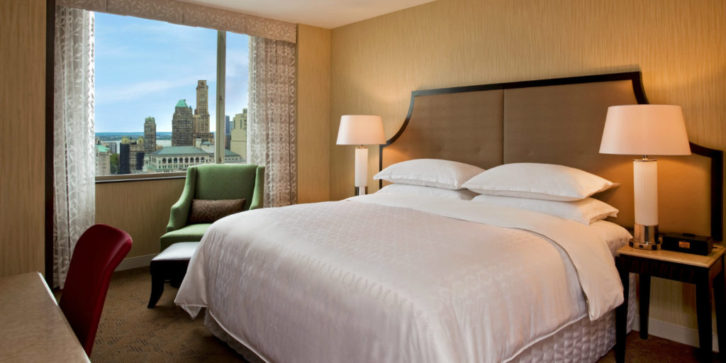 highrise hotel room with classic and elegant bedroom furniture overlooking a city view