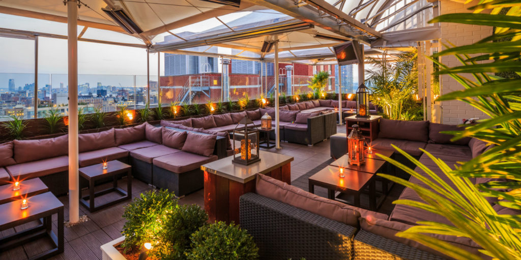 rooftop lounge area overlooking a city at dusk decorated with large purple and black outdoor sectional furniture