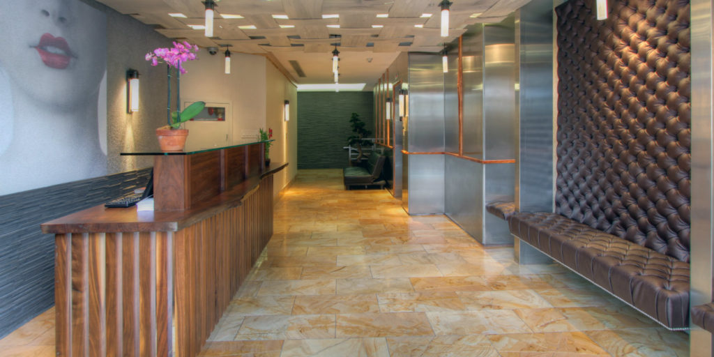 a modern hotel lobby with marble tile floors, leather benches and dark wooden check-in counter