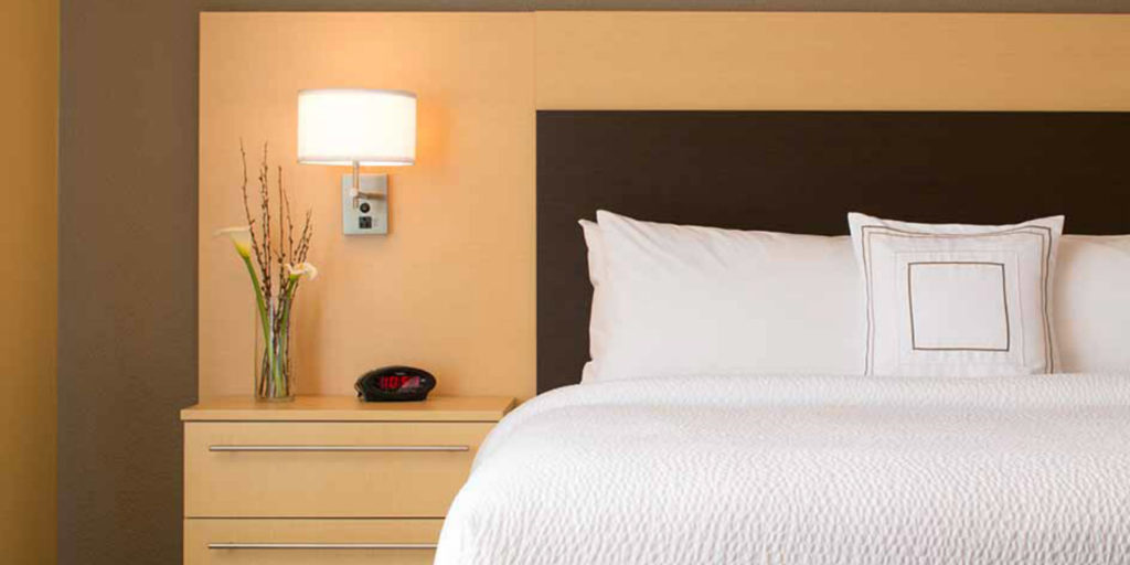 a kingsize bed with white bedding and a dark headboard next to a light wooden nightstand with alarm clock and white sconce lamp