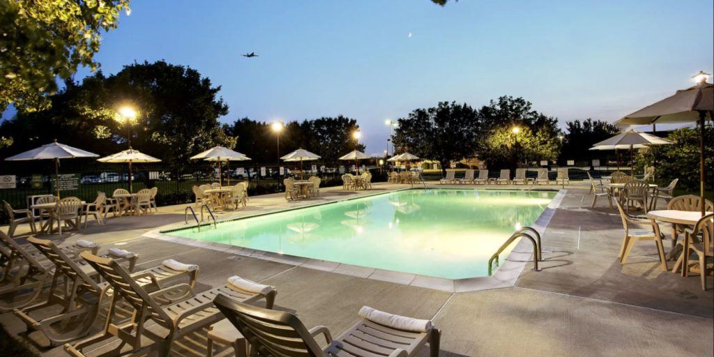 an outdoor swimming pool at dusk surrounded by patio chairs and tables