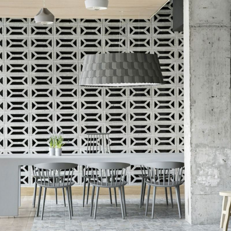 dining table for ten people set next to a concrete pillar and infront of a patterened concrete wall